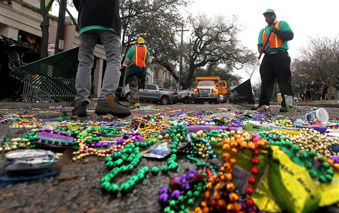 Cleaning up a bunch of beads after a Mardi Gras parade. Please note the public works trucks and personnel.