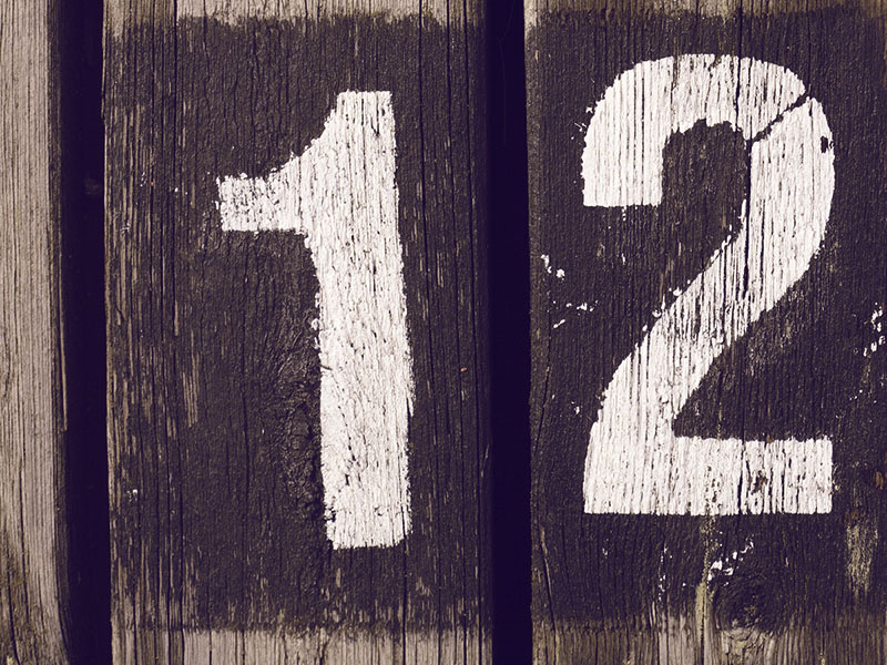 The number 1 and the number 2 painted on two boards, but put next to each other so it looks like 12.