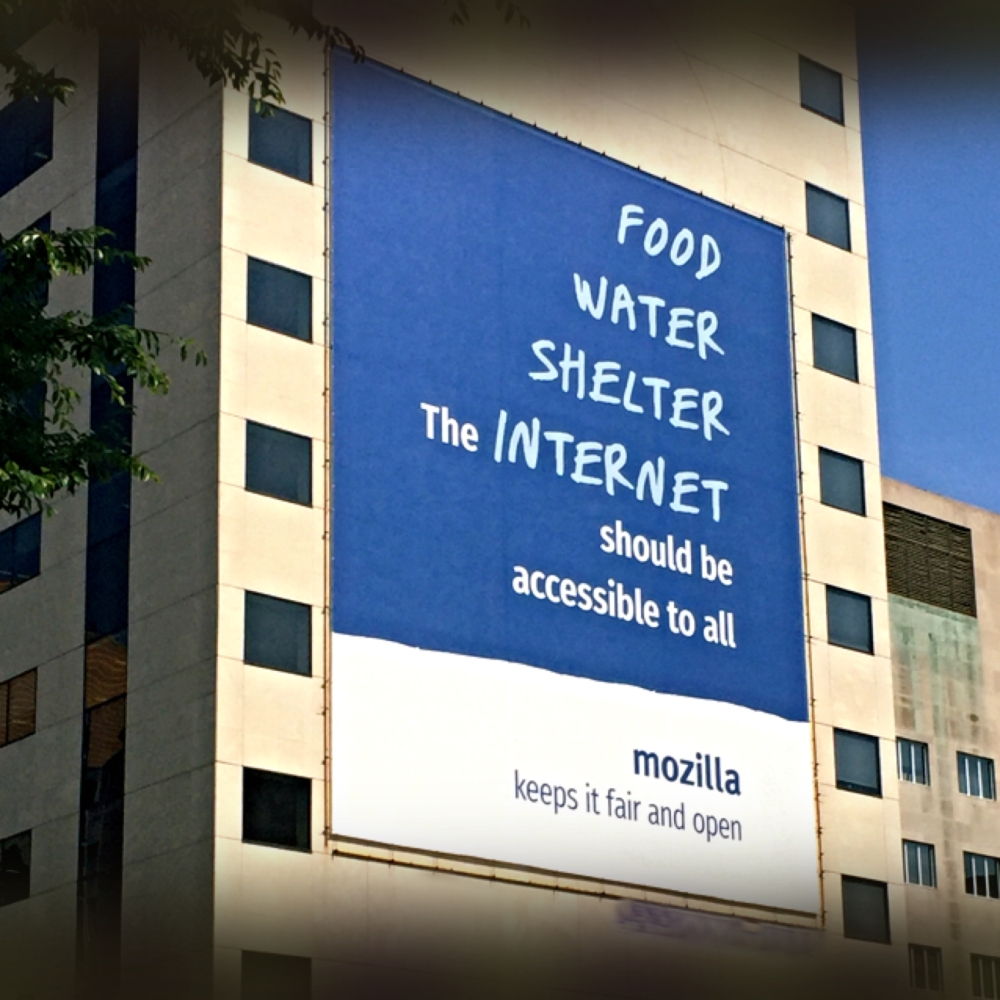 Huge sign on the side of the building from mozilla ranking Food Water Shelter The Internet