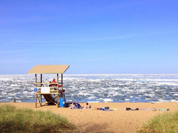 This is the shore of Lake Superior, in the Upper Peninsula of Michigan. People are at the beach sunbathing. Those are NOT whitecaps but ice flows. Brrrr!