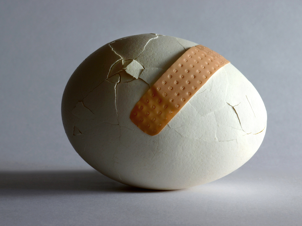 an egg with a bunch of cracks and an ineffective bandaid across a few of them.
