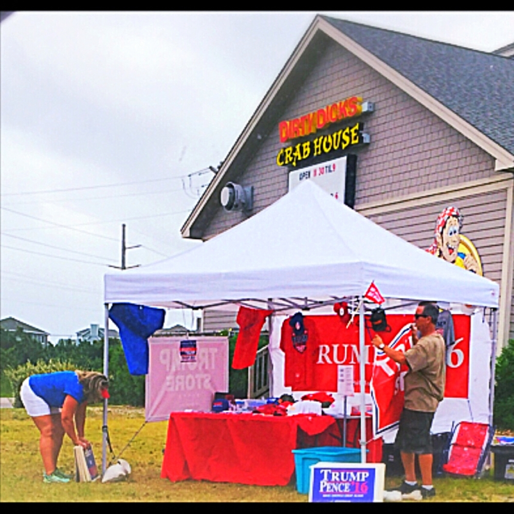 People setting up their booth of trump campaign booty in front of a restaurant with the motto, I got my crabs at Dirty Dick's.