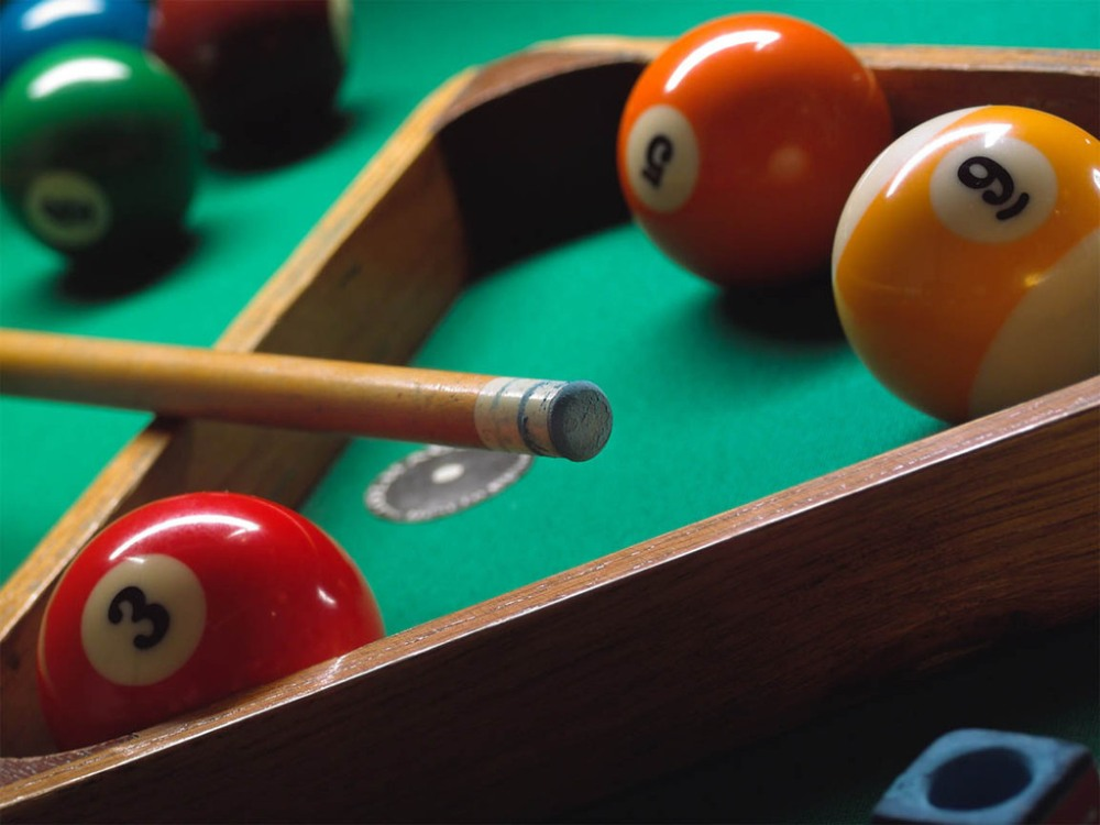 A triangle, a pool cue and a few balls inside the triangle and a few balls outside the triangle. The table is green. The balls in the triange are 3, 5 and 9. Nine is striped.