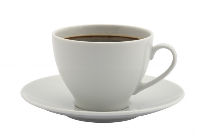 A cup of coffee in a white cup on a white saucer. I bet it's not decaf.