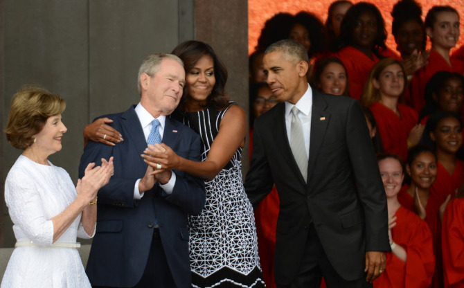 President Obama and Laura Bush watch first lady Michelle Obama embracing president George W. Bush at the dedication of the National Museum of African American History and Culture.