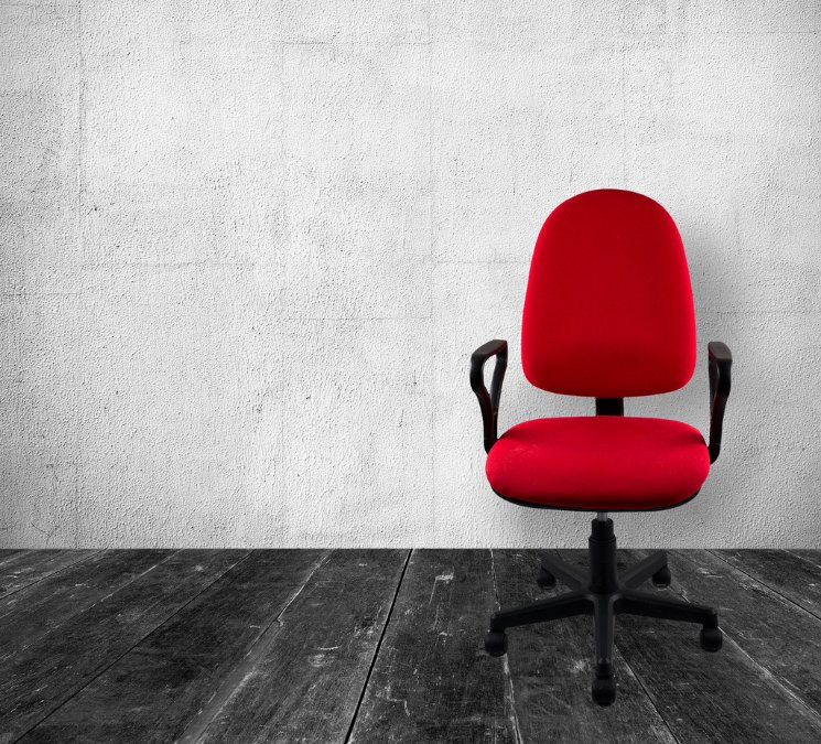 An empty office chair. The chair is red and it's in a rustic room.