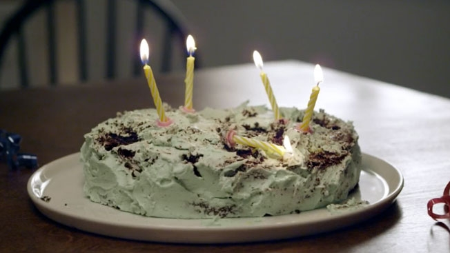 A almost collapsed cake with four lit birthday candles. The cake is greenish. With some chocolate cake poking through the frosting. What a mess. We didn't eat this. It's just a picture from the Internet.