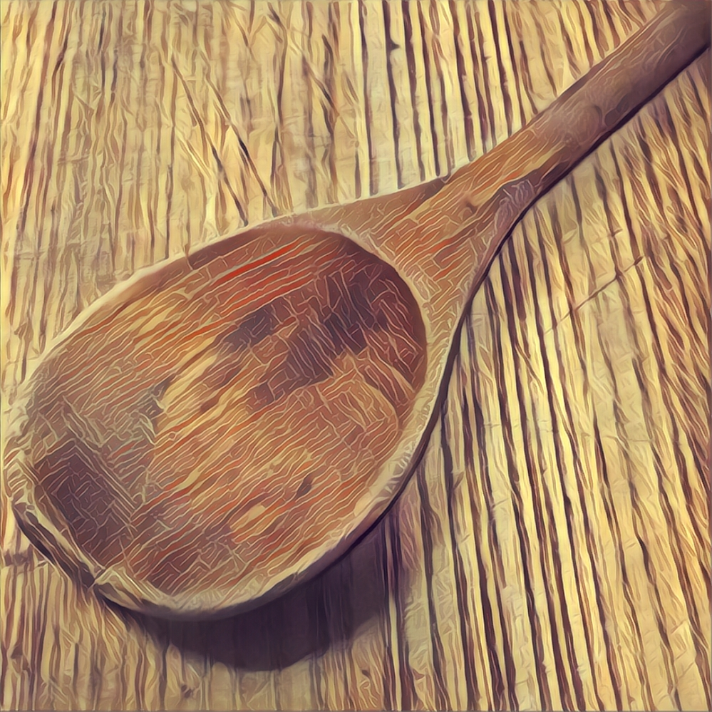 A worn wooden spoon on a worn wooden cutting board.