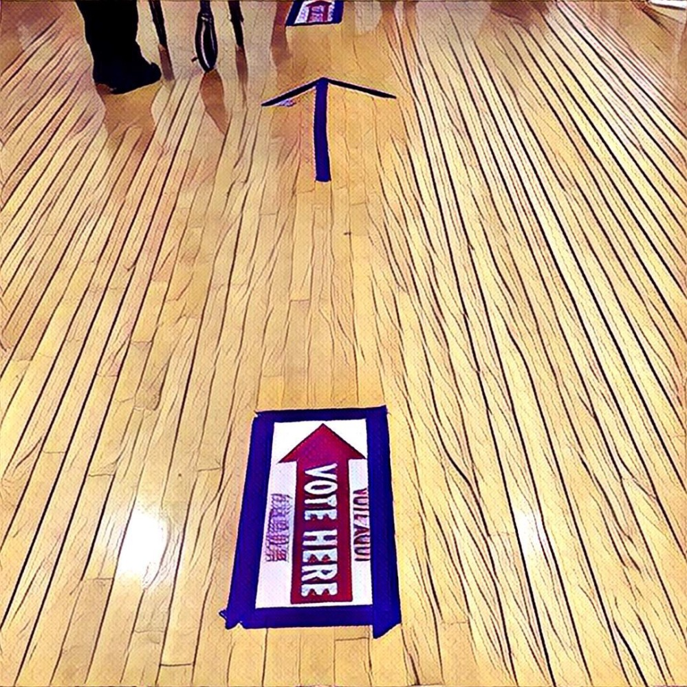 Voting sign taped to the floor of the gym.