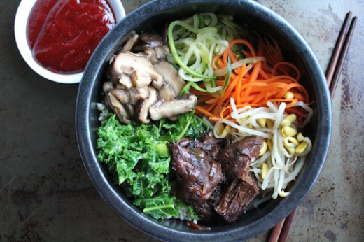 A bowl of beef bibimbap, with veggies. There's a pair of chopsticks and some red sauce on the side.