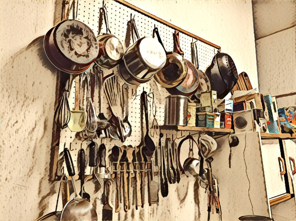 The wall of pots in our kitchen, hanging haphazardly on a pegboard wall. Circa now.
