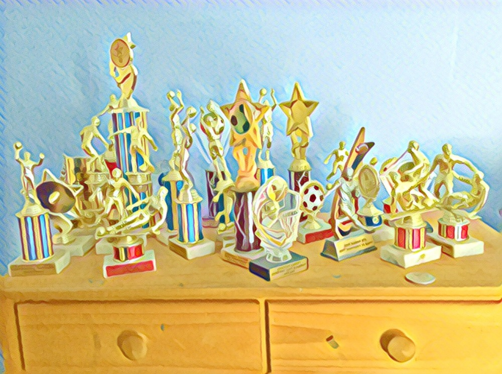 A dresser covered with two dozen trophies from basketball, soccer, rugby, baseball and football. Some personalized, most generic.