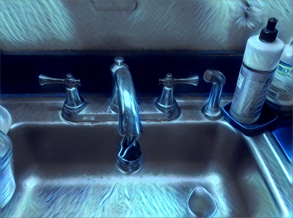 An old sink and faucet with an electric blue cast.