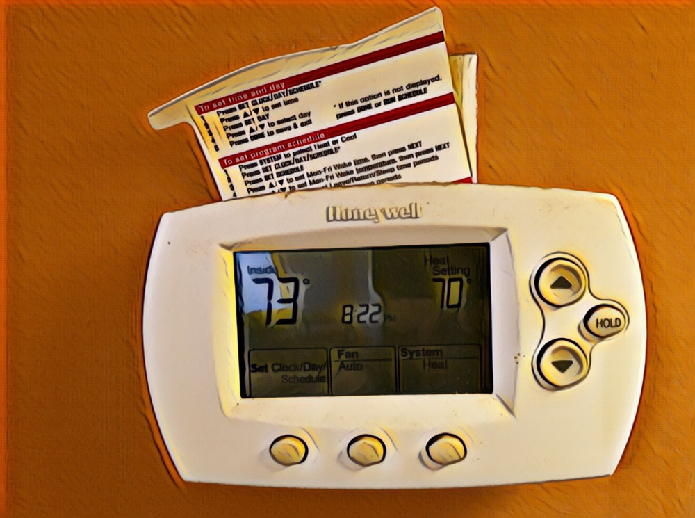 A Honeywell thermostat on an orange dining room wall.