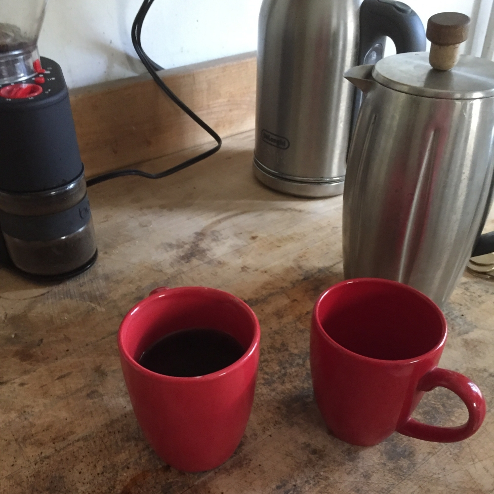 Two red mugs and a coffee setup.