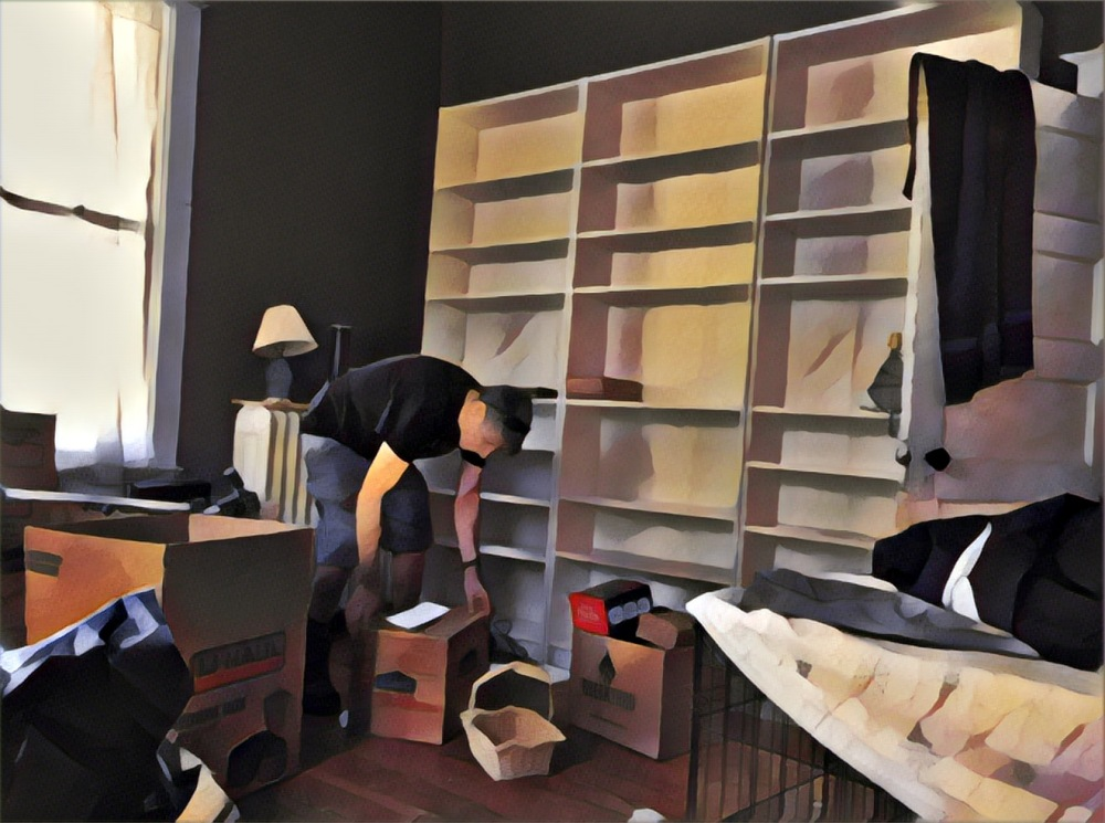 Guy packing a box in front of empty bookcases.